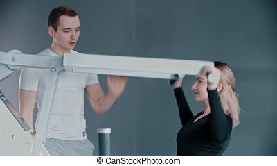 Training with fitness instructor in modern gym - a young woman training her hands on the modern simulator