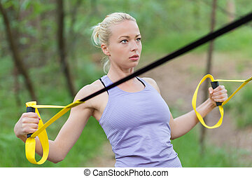 Training with fitness straps outdoors. - Young attractive...