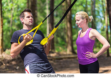 Training with fitness straps outdoors. - Young active people...