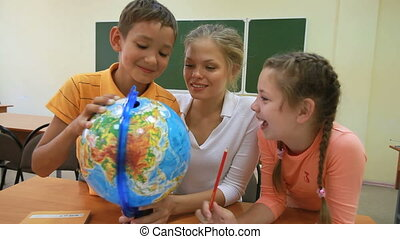 Training with globe - Two pupils examining globe with their...