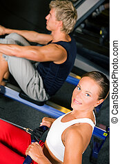 Training with rowing machine - Couple in the gym working out...