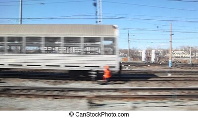 trains and railroad tracks with city on background from moving train