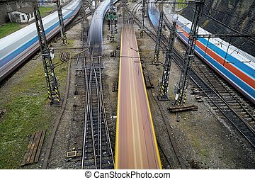 Trains in busy railroad station - Blurred motion of trains ...