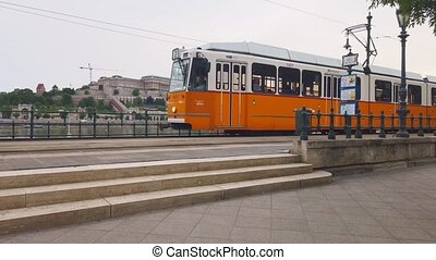 The iconic yellow 2 tram leaving the stop along the Danube river with Budapest Castle in the Background