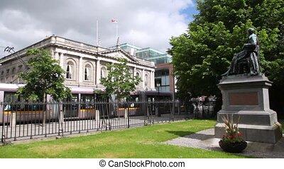 Tram passes near monument of sitting Sir Arthur Guinness in city center