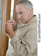trame porte, tournevis, utilisation, homme aîné