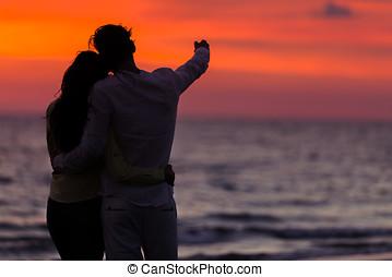 tramonto, silhouette, di, giovane coppia, amore, abbracciare, a, spiaggia