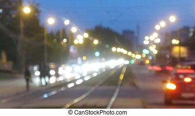 Trams go in middle of highway among stream of cars in evening