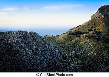 Tramuntana near Sa Calobra, lone house in the mountains at sunset, rocks, green pastures, mediterranean sea, blue sky, Mallorca, Spain.