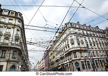 Modern public transportation with tramway or trolley cables criss-crossing at a busy street intersection contrasting with the old historic building architecture of European city, Lyon, France.
