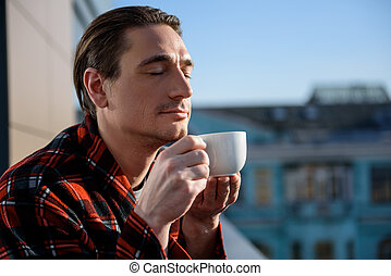 Tranquil adult man enjoying coffee outdoor