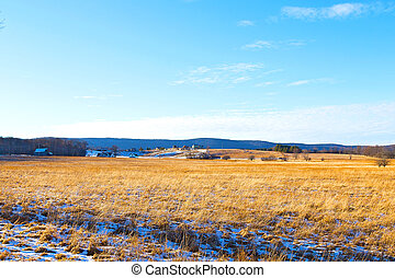 Tranquil countryside landscape in West Virginia. The snow is melting on the fields with a picturesque background of forest trees and farmhouses.