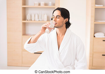 Tranquil guy is thirsty after massage