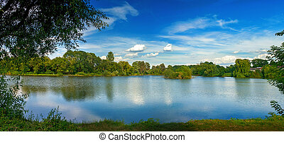 Tranquil landscape at a lake, with white clouds sky and the trees reflected in the clean blue water