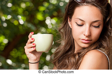 Tranquil moment - Smiling brunette beauty holding green cup ...