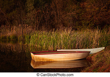 Tranquil scene of a small red and white fishing boat on a small rural pond at sunset with autumn foliage reflecting in the calm water