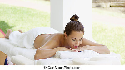 Tranquil spa customer relaxes on table