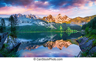 Tranquil summer scene on the Vorderer Gosausee lake in the Austrian Alps. Colorful sky reflected from mirror surface of lake. Austria, Europe.