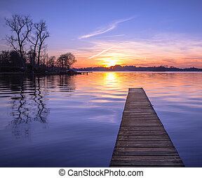 Tranquil Sunset reflecting in Water over Wooden Jetty in Groning
