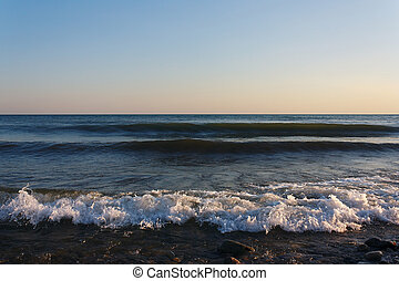 Tranquil surf waves on beach in the evening