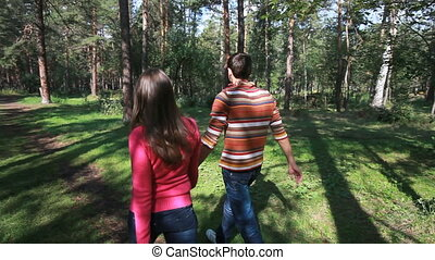 Tranquil walk - Young couple walking in wood