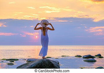 Tranquil woman in summer dress at seaside