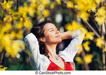 Tranquility - Carefree smiling woman behind leafs with arms...