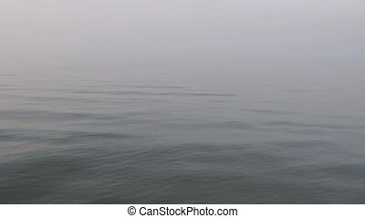 Tranquility waves on sea, calm and silence. Foggy weather, morning