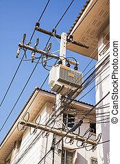 Transformers of an electrical post with powerlines against brigh