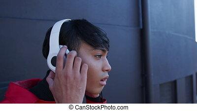 Transgender adult getting off the headphones - Side view ...