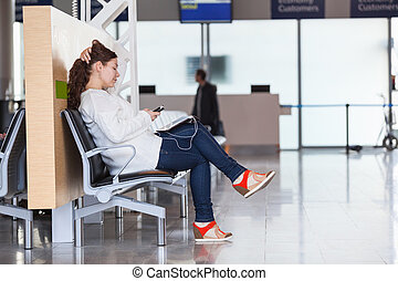 Transit passenger with devices waiting flight in airport lounge