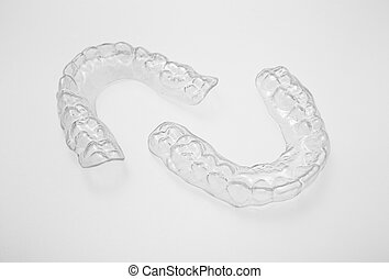 Translucent upper and lower essix retainers on a gray...