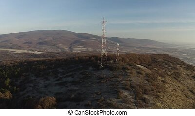 Communication transmitter tower on a hill in the countryside aerial view drone footage. Cellphone network antennas.