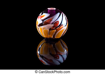 Transparent and colour glass bead with reflection on black...