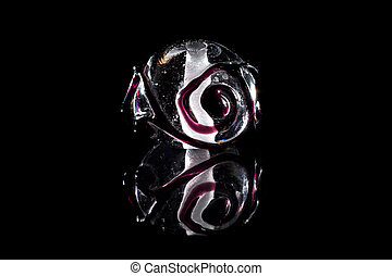 Transparent and pink glass bead with reflection on black...