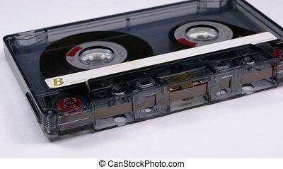 Transparent Audio Cassette Rotates on White Background....
