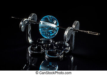 Transparent blue glass bead on stand