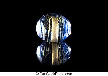 Transparent blue glass bead with reflection on black...