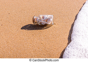 Transparent bottle with shells on the beach in the waves