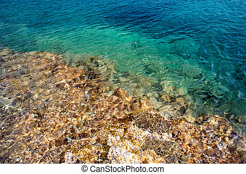 Transparent clear water and stones with sunlight reflection