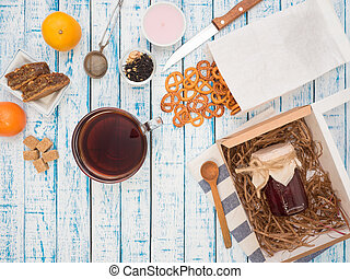 Transparent cup of black tea, cookies and lemon on a wooden table