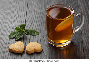 transparent cup of tea with lemon, mint and cookies on a wooden table