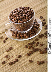 Transparent cup with coffee grains on a background of a mat