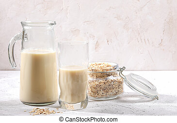 Transparent decanter and glass of oat milk and jar with oat flakes on white background.