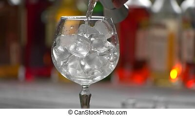 Transparent drink slowly pouring. Wineglass filled with ice....