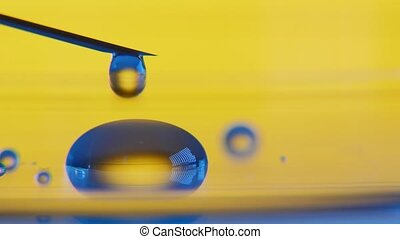 Transparent drops of water plash from a syringe forming a small pool