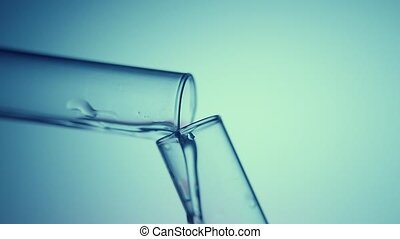 Transparent fluid flows from one test tube into another in a chemicallaboratory