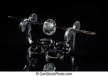 Transparent glass bead on stand on black background