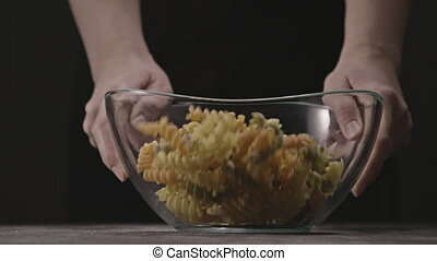 Transparent glass bowl in a woman's hands with pouring raw colorful Italian pasta on a wooden rustic table on a black. Slow motion, Full HD video, 240fps, 1080p.