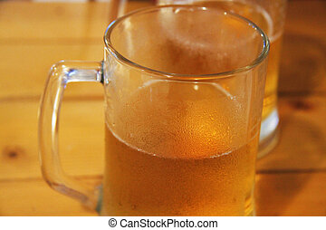 Transparent glass mug with beer on wooden table in cafe